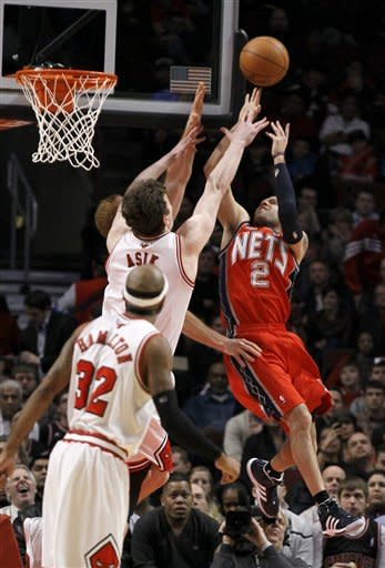 New Jersey Nets guard Jordan Farmar (2) shoots over Chicago Bulls center Omer Asik, as Richard Hamilton (32) watches during the second quarter of an NBA basketball game Monday, Jan. 23, 2012, in Chicago. (AP Photo/Charles Rex Arbogast)