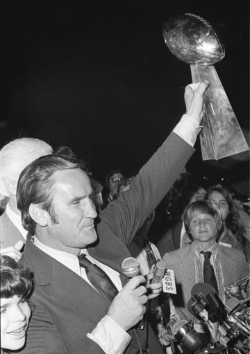 FILE - In this Jan. 15, 1973, file photo, Miami Dolphins coach Don Shula waves the Super Bowl trophy for fans as they arrive in Miami after defeating the Washington Redskins in Los Angeles in Super Bowl VII. Shula's son David looks on at right. Shula, who won the most games of any NFL coach and led the Miami Dolphins to the only perfect season in league history, died Monday, May 4, 2020, at his home in Indian Creek, Fla., the team said. He was 90. (AP Photo/file)