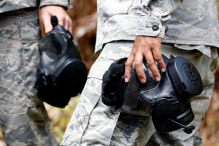Soldiers of the Hawaii National Guard carry gas masks in Leilani Estates during ongoing eruptions of the Kilauea Volcano in Hawaii, U.S., May 18, 2018. REUTERS/Terray Sylvester
