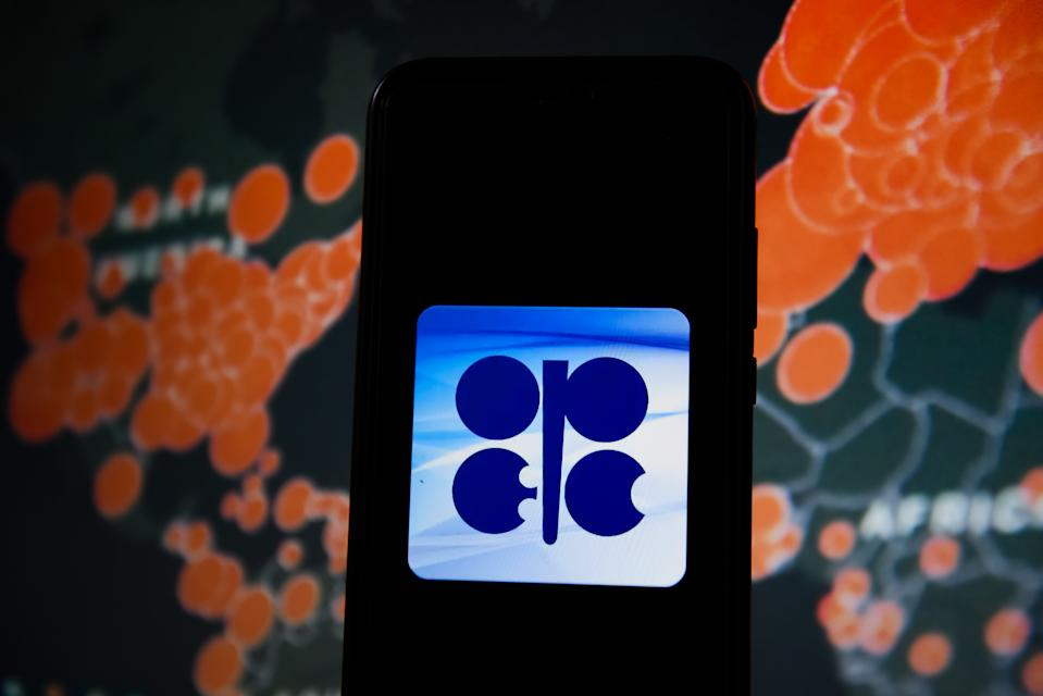 POLAND - 2020/03/19: In this photo illustration an OPEC logo seen displayed on a smartphone with a World map of COVID 19 epidemic on the background. (Photo Illustration by Omar Marques/SOPA Images/LightRocket via Getty Images)