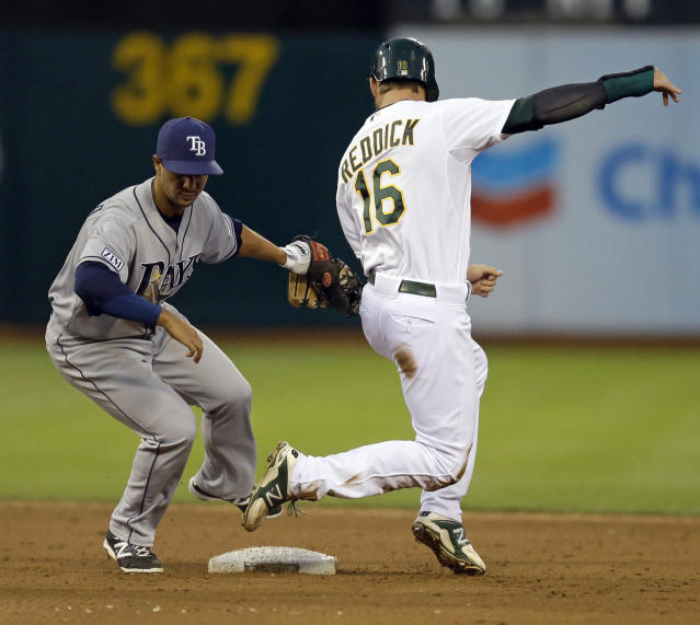 Tampa Bay Rays Cole Figueroa, left, tags out Oakland Athletics' Josh Reddick who was caught off base in the second inning of a baseball game Tuesday, Aug. 5, 2014, in Oakland, Calif. (AP Photo/Ben Margot)