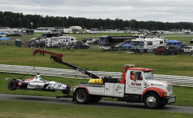 Track workers remove the wrecked car of Pietro Fittipaldi during the IndyCar auto race at Pocono Raceway, Sunday, Aug. 19, 2018, in Long Pond, Pa. (AP Photo/Matt Slocum)