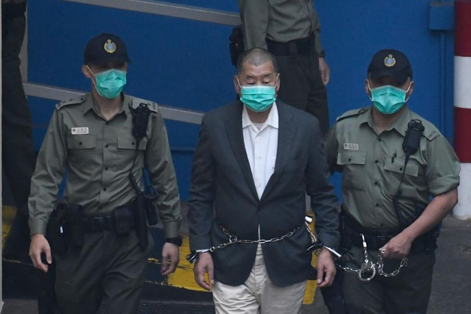 Owner of Apple Daily Newspaper Jimmy Lai is seen shackled as prison guards escort him to a prison van at Lai Chi Kok Reception Center in Hong Kong, China.