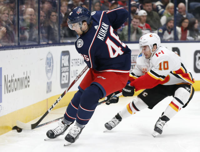 Columbus Blue Jackets' Dean Kukan, left, of Switzerland, tries to clear the puck as Calgary Flames' Derek Ryan defends during the first period of an NHL hockey game Saturday, Nov. 2, 2019, in Columbus, Ohio. (AP Photo/Jay LaPrete)