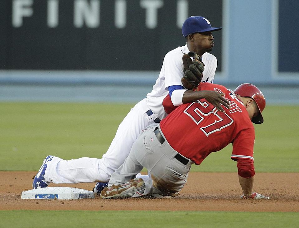 Los Angeles Dodgers second baseman Dee Gordon, top, watches his throw to first base after forcing out Los Angeles Angels' Mike Trout during the first inning of a baseball game on Tuesday, Aug. 5, 2014, in Los Angeles. Albert Pujols was out at first. (AP Photo/Jae C. Hong)