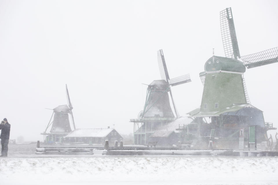 A man takes pictures at the Zaans Museum in Zaandam, as snow and strong winds pounded The Netherlands, Sunday, Feb. 7, 2021. (AP Photo/Peter Dejong)