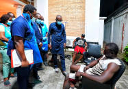 In this photo released by the Lagos State government press, governor Babajide Sanwo-Olu, centre, visit victims injured in last night's protests in a hospital in Lagos, Nigeria, Wednesday Oct. 21, 2020. Nigerians protesting against police brutality stayed on the streets in Lagos on Wednesday, breaking the government curfew following a night of chaotic violence in which demonstrators were fired upon, sparking global outrage. (Lagos State government press Via AP)