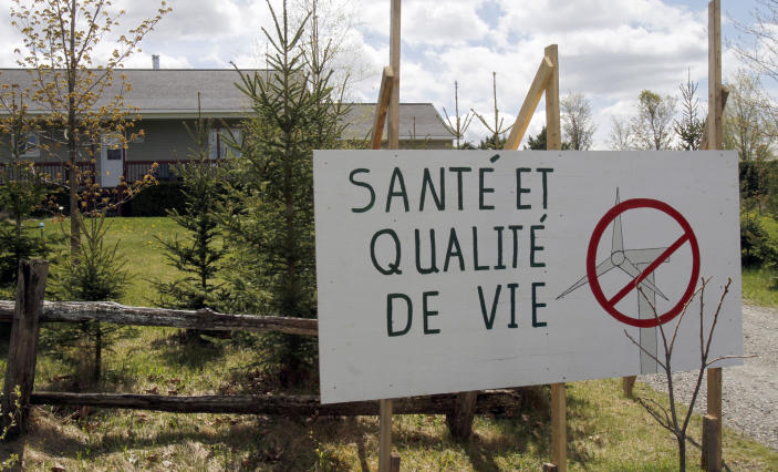 A resident has a sign opposing wind development in Stanstead, Quebec on Friday, May 11, 2012. A Vermont wind power developer and two dairy farmers in the border community of Derby Line say they've been surprised at the level of opposition to a plan to build two turbines that has been coming from the Quebec town of Stanstead.(AP Photo/Toby Talbot)