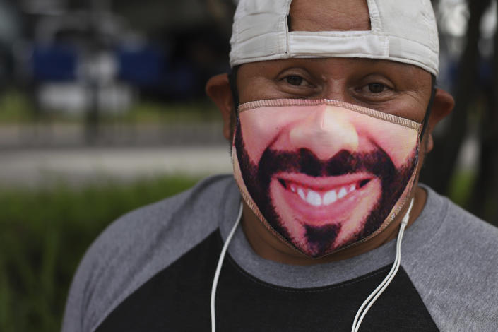 Fabian Santos, a street vendor and supporter of El Salvador's President Nayib Bukele poses with a Bukele mask outside a vaccination center in San Salvador, El Salvador, Tuesday, June 22, 2021. El Salvador has already covered a little more than a million people vaccinated with the first dose of the vaccine and this week announced that people over the age of 35 can now be vaccinated. (AP Photo/Salvador Melendez)