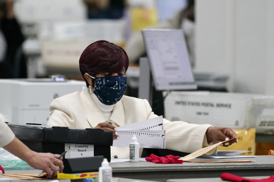 FILE - In this Nov. 4, 2020 file photo, absentee ballots are processed at the central counting board in Detroit. This year, Republicans across the country have zeroed in on mail voting and enacted new limits on a process that exploded in popularity during the pandemic. (AP Photo/Carlos Osorio, File )