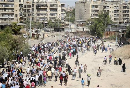 A view is seen of civilians as they walk at the Karaj al-Hajez crossing, a passageway separating Aleppo's Bustan al-Qasr, which is under the rebels' control and Al-Masharqa neighborhood, an area controlled by the regime, September 10, 2013. REUTERS/Ammar Abdullah