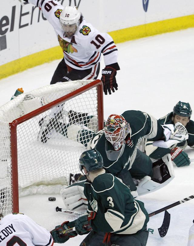 Minnesota Wild goalie Ilya Bryzgalov, center, and Wild center Charlie Coyle (3) are near as a shot by Chicago Blackhawks left wing Patrick Sharp (10) goes in during the first period of Game 4 of an NHL hockey second-round playoff series in St. Paul, Minn., Friday, May 9, 2014. (AP Photo/Ann Heisenfelt)
