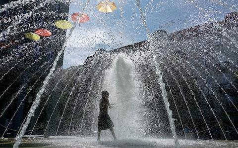<span>A boy plays in a fontaine in Berlin, Germany</span> <span>Credit: AP </span>
