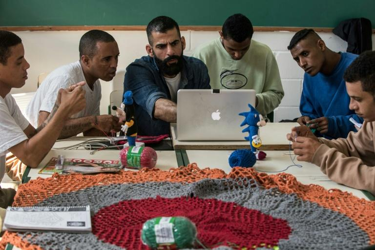 Brazilian designer and craftsman Gustavo Silvestre (C) teaches crochet to inmates in the Adriano Marrey maximum security penitentiary near Sao Paulo