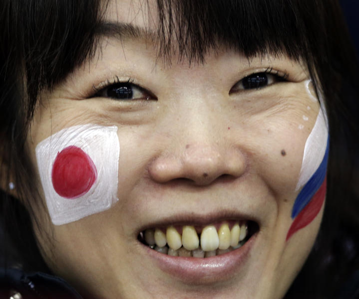 A skating fan, with the Russian and Japanese flags painted on her face, watches the men's 500-meter speedskating race at the Adler Arena Skating Center at the 2014 Winter Olympics, Monday, Feb. 10, 2014, in Sochi, Russia. (AP Photo/Matt Dunham)