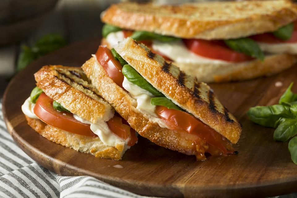 """<p>A simple grilled cheese is one of those <a href=""""https://www.thedailymeal.com/cook/forgotten-childhood-dinners?referrer=yahoo&category=beauty_food&include_utm=1&utm_medium=referral&utm_source=yahoo&utm_campaign=feed"""" rel=""""nofollow noopener"""" target=""""_blank"""" data-ylk=""""slk:classic childhood dinners"""" class=""""link rapid-noclick-resp"""">classic childhood dinners</a>. This Caprese-inspired grilled cheese includes fresh tomato, mozzarella and basil to make this sandwich a little more adult, but it's still a lot of fun.</p> <p><a href=""""https://www.thedailymeal.com/best-recipes/caprese-grilled-cheese?referrer=yahoo&category=beauty_food&include_utm=1&utm_medium=referral&utm_source=yahoo&utm_campaign=feed"""" rel=""""nofollow noopener"""" target=""""_blank"""" data-ylk=""""slk:For the Caprese Grilled Cheese recipe, click here."""" class=""""link rapid-noclick-resp"""">For the Caprese Grilled Cheese recipe, click here.</a></p>"""