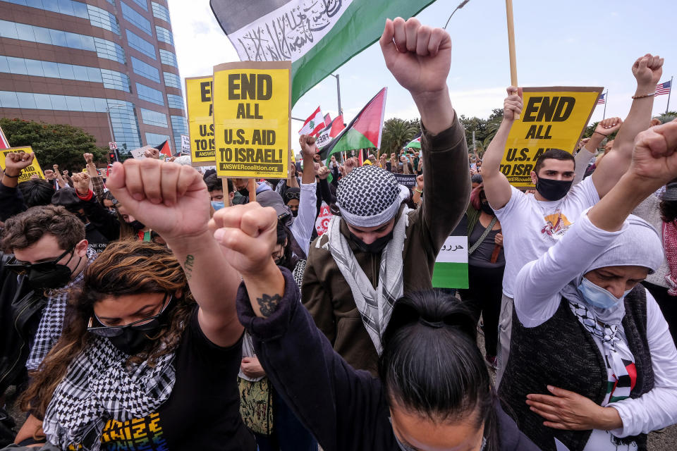 Demonstrators raise their fists during a protest outside the Federal Building against Israel and in support of Palestinians, Saturday, May 15, 2021 in the Westwood section of Los Angeles. (AP Photo/Ringo H.W. Chiu)