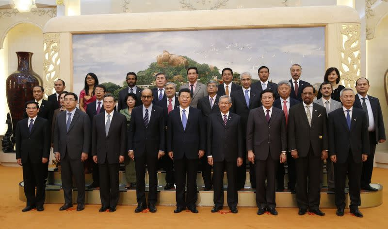 China's President Xi Jinping poses for photos with the guests at the Asian Infrastructure Investment Bank launch ceremony at the Great Hall of the People in Beijing