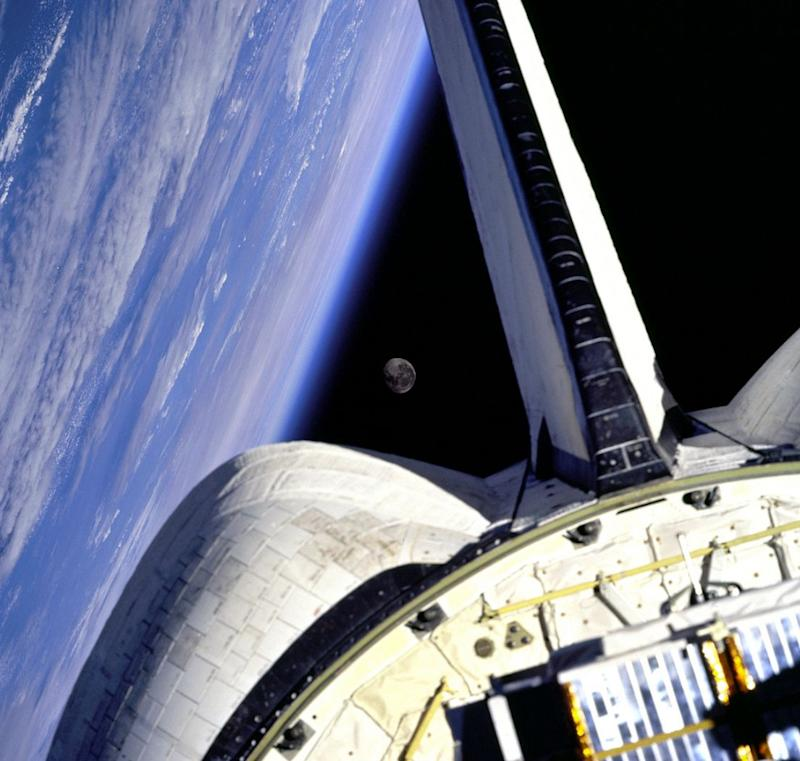 Earth and its Moon are nicely framed in this image taken from the aft windows of the Space Shuttle Discovery in 1998. Discovery - on mission STS-95 - was flying over the Atlantic Ocean at the time this image was taken.