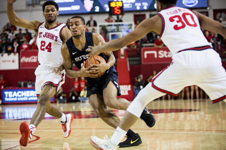 Butler guard Aaron Thompson (2) pushes through St. John's guards Nick Rutherford (24) and LJ Figueroa (30) during the first half of NCAA college basketball game Tuesday, Dec. 31, 2019, in New York. (AP Photo/Julius Constantine Motal)