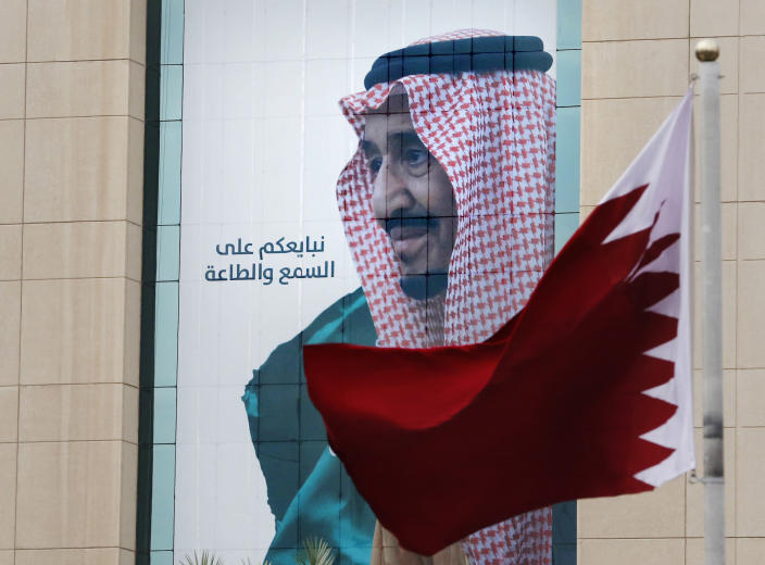 """FILE - In this Dec. 9, 2019, file photo, a Qatari flag flies in front of a banner showing Saudi King Salman with Arabic writing that reads, """"We pledge you to listen and obey"""" at a trade center in Riyadh, Saudi Arabia, ahead of the Gulf Cooperation Council """"GCC"""", 40th summit. Kuwait's foreign ministry on Monday, Jan. 4, 2021, announced that Saudi Arabia will lift a years-long embargo on Qatar, opening its air and land borders in the first steps toward ending the Gulf crisis.(AP Photo/Amr Nabil, File)"""