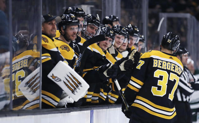 Boston Bruins center Patrice Bergeron (37) is congratulated by teammates after his goal against the Minnesota Wild during the second period of an NHL hockey game in Boston, Tuesday, Jan. 8, 2019. (AP Photo/Charles Krupa)