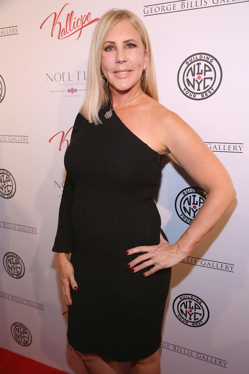 Vicki Gunvalson poses on a red carpet with one hand on her hip wearing a one sleeved black dress