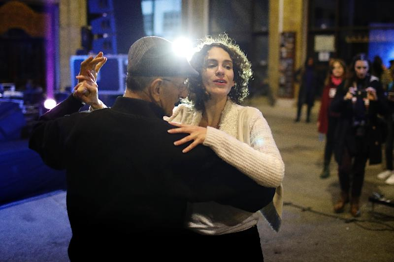 """A Greek Cypriot and Turkish Cypriot dance together during the """"Countdown to Peace"""" music event organised in the northern part of Nicosia's old city, in the self-proclaimed Turkish Republic of Northern Cyprus (AFP Photo/Florian CHOBLET)"""