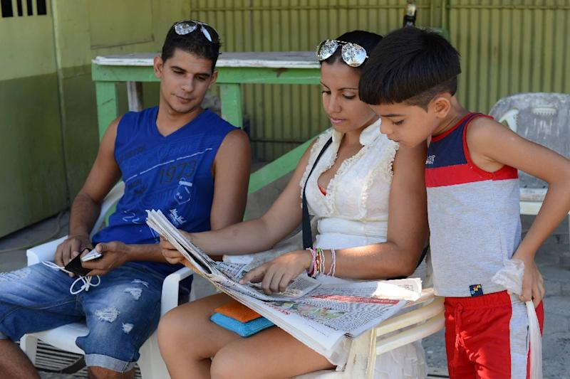 Cuban migrants read the news in a shelter in Liberia on January 13, 2016 (AFP Photo/Carlos Gonzalez )