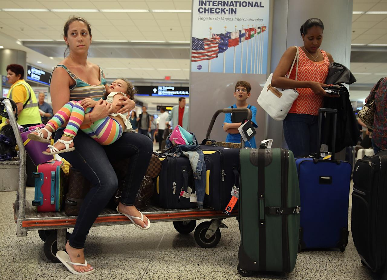MIAMI, FL - APRIL 16:  American Airlines passenger, Lilly Tajman holds her daughter, Sofie Tajman as they wait in line for a flight at Miami International Airport on April 16, 2013 in Miami, Florida. Thousands of American Airlines travelers became stranded today when the airline was forced to ground all its flights after a nationwide problem with its computer systems  (Photo by Joe Raedle/Getty Images)