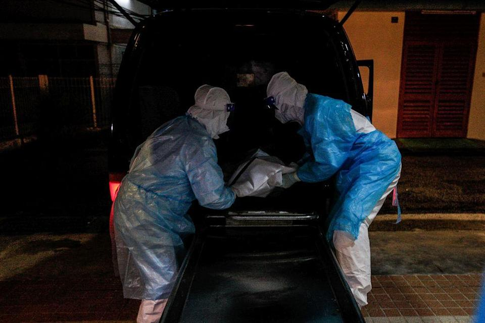 Forensics personnel unload the body of a recently deceased Covid-19 patient at the Penang General Hospital, August 24, 2021. — Picture by Sayuti Zainudin