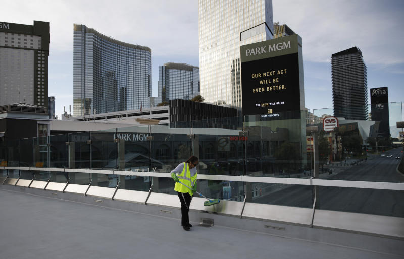 A worker cleans along the Las Vegas Strip devoid of the usual crowds as casinos and other business are closed due to the coronavirus outbreak, Tuesday, March 31, 2020, in Las Vegas. (AP Photo/John Locher)