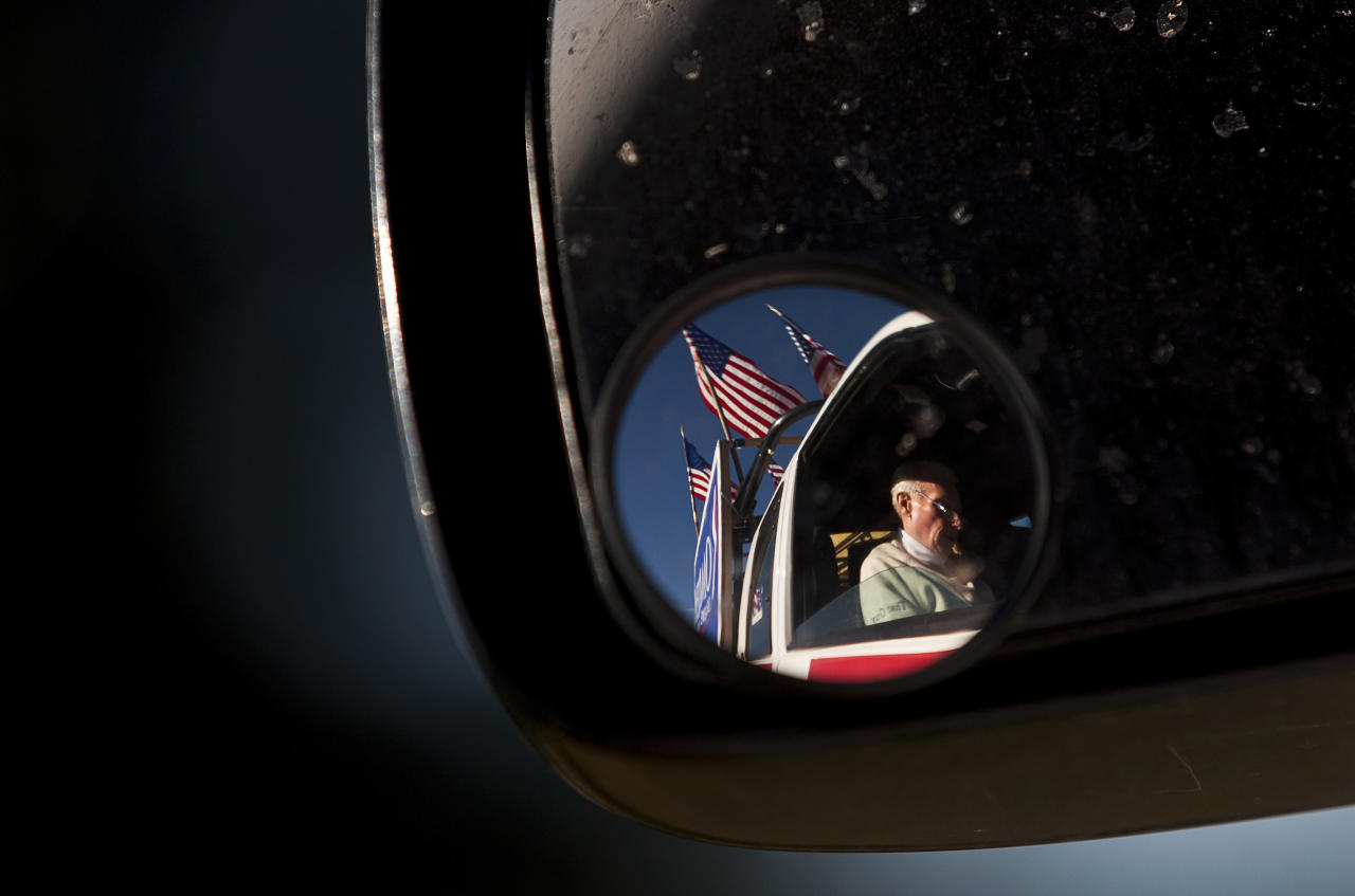 Supporter Jim Wilson is seen through a mirror as he sits in his pick up truck before a campaign stop for Republican presidential candidate and former Massachusetts Governor Mitt Romney at the University of South Carolina Aiken in Aiken, South Carolina January 13, 2012. REUTERS/Chris Keane