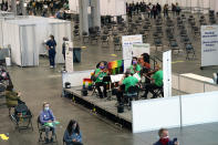 A string quartet performs at the Jacob K. Javits Convention Center vaccination site, Tuesday, March 23, 2021, in New York. The music is part of a series of daily, two-hour midday concerts from a collaboration between the nonprofit group Sing for Hope and violinist Victoria Paterson, who started her own nonprofit, Music and Medicine. (AP Photo/Kathy Willens)