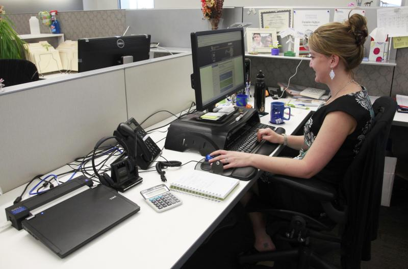 Danelle Hutton works on her laptop computer (left) in her open cubicle at the U.S. National Renewable Energy Laboratory Research Support Facility (RFS) in Golden