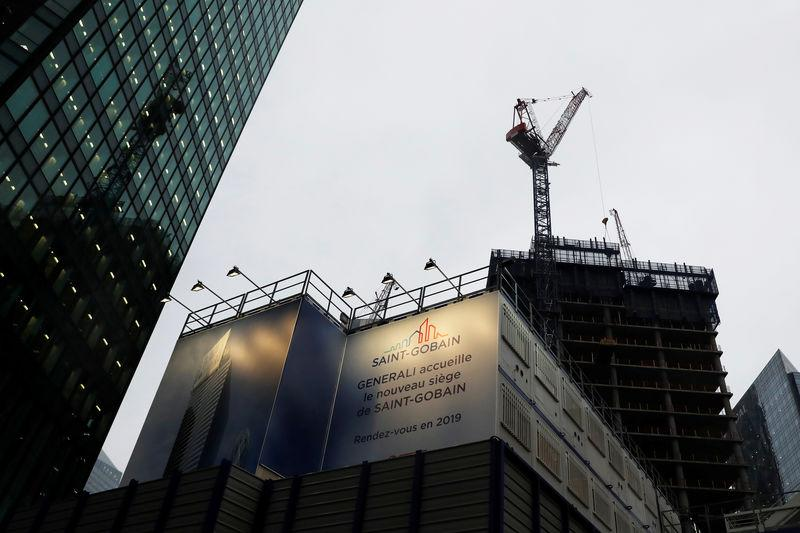 FILE PHOTO: The logo of Saint-Gobain is seen on a banner on a building construction site in the financial and business district of La Defense, outside Paris