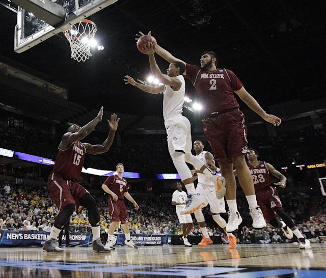 San Diego State's Aqeel Quinn, center, shoots against New Mexico State's Sim Bhullar (2) during the first half of a second-round game of the NCAA men's college basketball tournament in Spokane, Wash., Thursday, March 20, 2014. (AP Photo/Young Kwak)