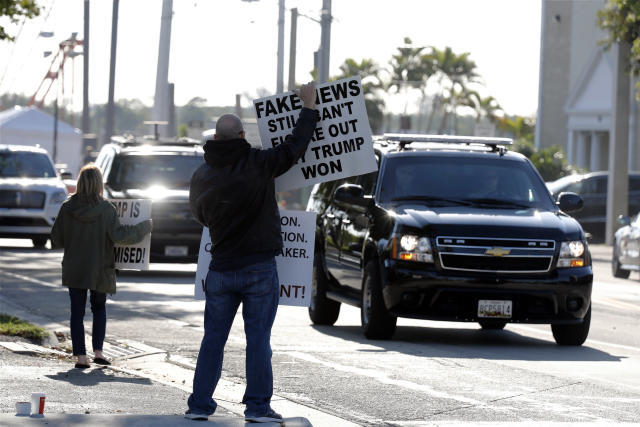 People hold signs as the motorcade of President Donald Trump passes on Saturday, March 23, 2019, in West Palm Beach, Fla. Special counsel Robert Mueller closed his long and contentious Russia investigation with no new charges, ending the probe that has cast a dark shadow over Trump's presidency. (AP Photo/Terry Renna)