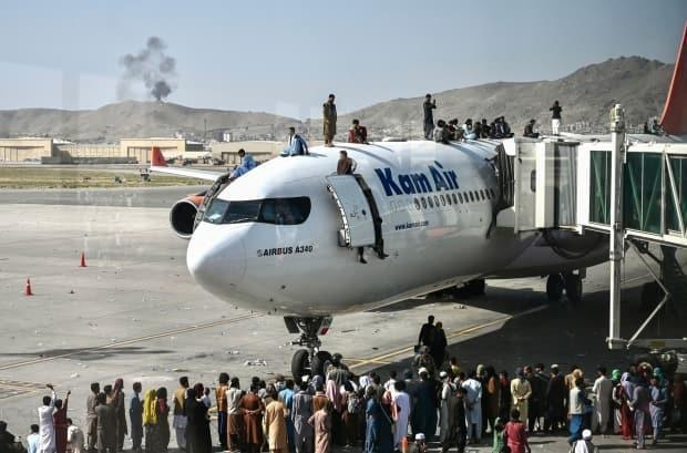 Afghan people desperate to flee the Taliban climb atop a plane at the Kabul airport on August 16, 2021. Thousands of people mobbed the city's airport trying to escape the group's feared hardline brand of Islamist rule. (Wakil Kohsar/AFP/Getty Images - image credit)