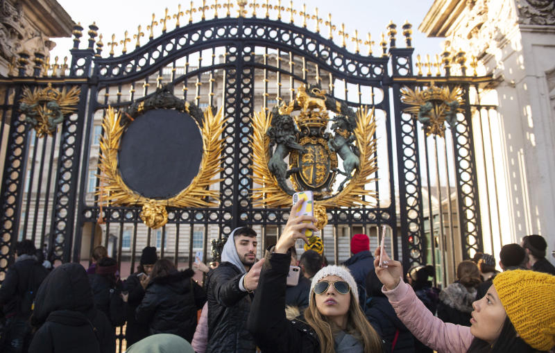 "Tourists take photos outside the gates of Buckingham Palace, following a statement by Britain's Queen Elizabeth II and Buckingham Palace, in London, Sunday Jan. 19, 2020. Buckingham Palace says Prince Harry and his wife, Meghan, will no longer use the titles ""royal highness"" or receive public funds for their work under a deal that allows them to step aside as senior royals.  (Dominic Lipinski/PA via AP)"