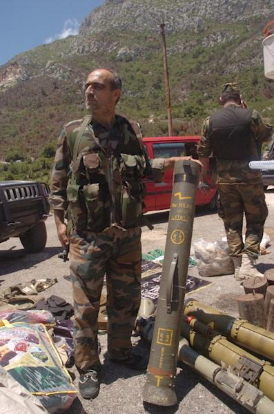 A handout picture released by the official Syrian Arab News Agency (SANA) shows member of the Syrian army showing off a rocket launcher in the town of Kasab, on June 15, 2014 (AFP Photo/-)
