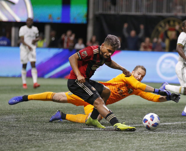 Atlanta United forward Josef Martinez (7) beats Portland Timbers goalkeeper Jeff Attinella (1) to score a goal during the first half of the MLS Cup championship soccer game, Saturday, Dec. 8, 2018, in Atlanta. (AP Photo/Todd Kirkland)