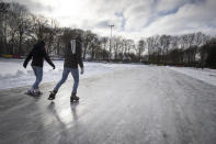 Skaters enjoy a man-made ice track in Doorn, Netherlands, Tuesday, Feb. 9, 2021. With freezing temperatures forecast for more than a week in the Netherlands, ice fever is sweeping the nation, offering a welcome respite from grim coronavirus news while also creating a challenge for authorities trying to uphold social distancing measures. (AP Photo/Peter Dejong)