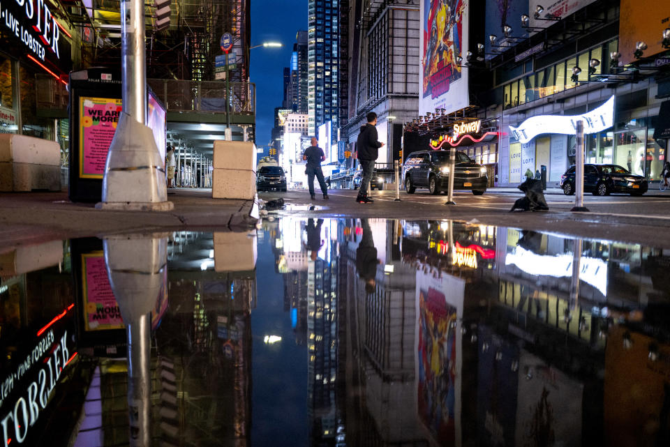 The lights of Times Square in New York are reflected in standing water Thursday, Sept 2, 2021, as Hurricane Ida left behind not just water on city streets but wind damage and severe flooding along the Eastern seaboard. (AP Photo/Craig Ruttle)