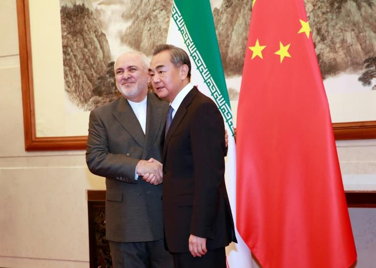Chinese Foreign Minister Wang Yi shakes hands with Iranian Foreign Minister Mohammad Javad Zarif at the Diaoyutai State Guesthouse in Beijing