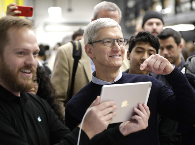 Apple CEO Tim Cook tells reporters they should see what is on the new iPad 9.7-inch screen at an Apple educational event at Lane Technical College Prep High School Tuesday, March 27, 2018, in Chicago. Apple will report earnings after the market close on Tuesday.  (AP Photo/Charles Rex Arbogast)