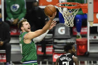 Dallas Mavericks guard Luka Doncic, left, goes up for a basket past Los Angeles Clippers guard Patrick Beverley during the first half of an NBA basketball game in Los Angeles, Sunday, Dec. 27, 2020. (AP Photo/Kyusung Gong)