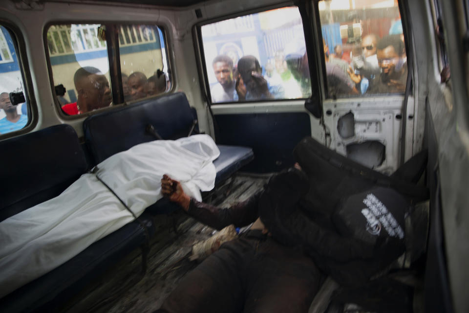 People look into the window of a police car carrying the bodies of two people killed in a shooting with police in Port-au-Prince, Haiti, Thursday, July 8, 2021. According to Police Chief Leon Charles, the two dead are suspects in the assassination of Haitian President Jovenel Moïse. (AP Photo/Joseph Odelyn)