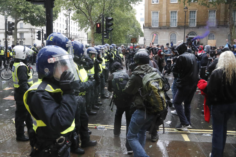 Police faces demonstrators after scuffles during a Black Lives Matter march in London, Saturday, June 6, 2020, as people protest against the killing of George Floyd by police officers in Minneapolis, USA. Floyd, a black man, died after he was restrained by Minneapolis police while in custody on May 25 in Minnesota. (AP Photo/Frank Augstein)