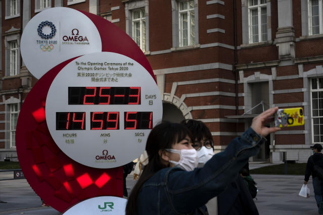 Two women take a selfie with a Tokyo 2020 countdown clock displaying the current date and time outside Tokyo Station, Wednesday, March 25, 2020, in Tokyo. Not even the Summer Olympics could withstand the force of the coronavirus. After weeks of hedging, the IOC took the unprecedented step of postponing the world's biggest sporting event, a global extravaganza that's been cemented into the calendar for more than a century. (AP Photo/Jae C. Hong)